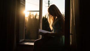 Donna seduta davanti finestra, in controluce con le gambe incrociate.Legge un libro su mindfulness e accettazione del proprio corpo
