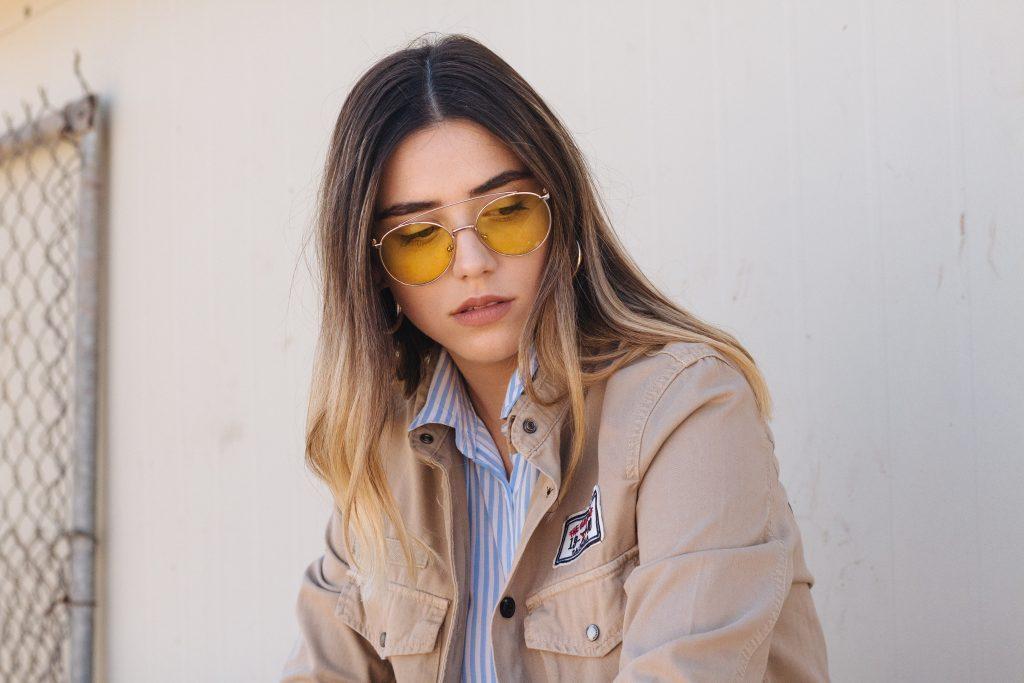 foto di donna a tre quarti. Indossa occhiali tondi e lenti gialle, una camicia a righe bianche blu e una giacca casual marrone. Guarda in basso. impara come scegliere gli abiti giusti da tenere