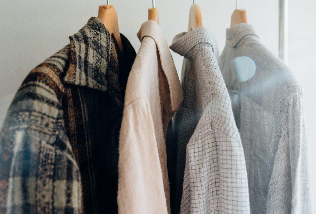 foto in primo piano di uno stand per abbigliamento in cui sono appese tre camicie e una giacca. La giacca è in panno e a scacchi. Impara come scegliere gli abiti giusti da tenere