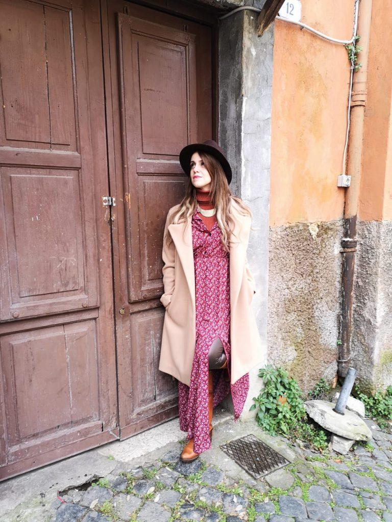 Donna in posa davanti ad un portone antico romano. Indossa abito lungo a fiori, un cappotto color cammello e un cappello marrone. Riprendere in mano la propria vita parte da chi sei veramente