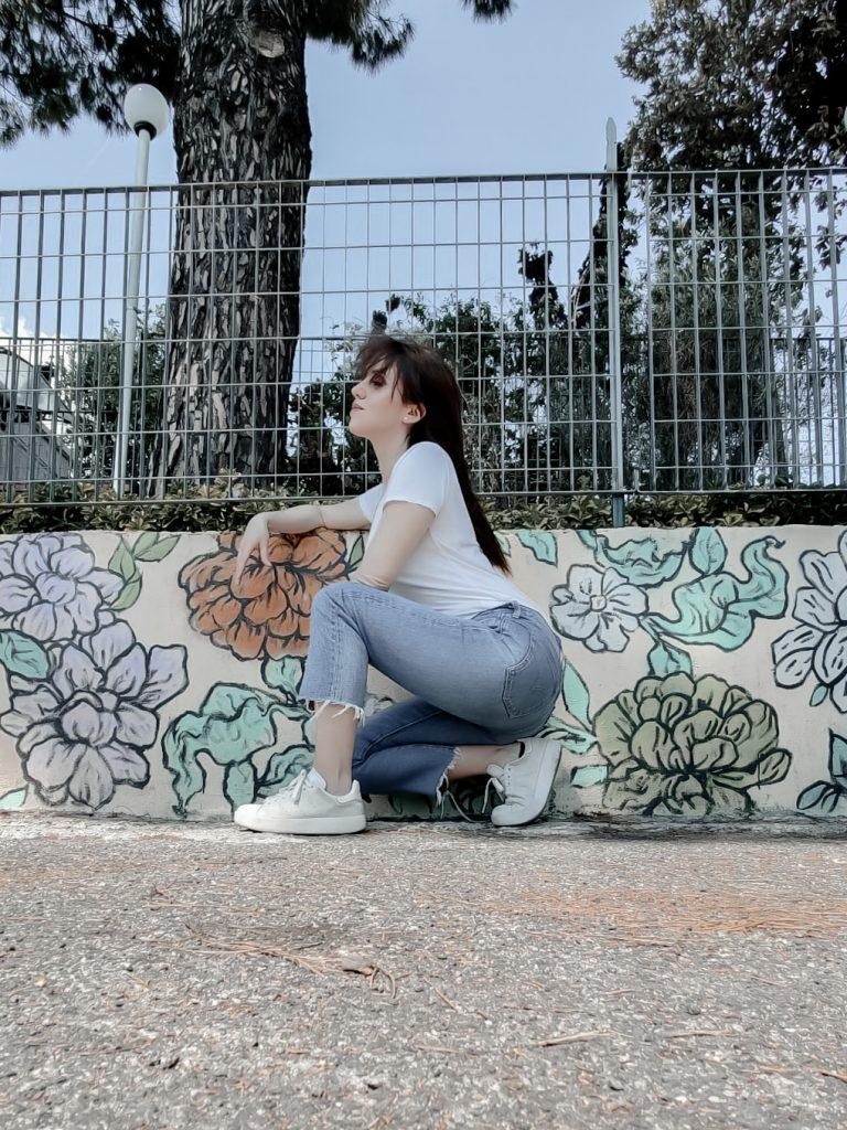 donna piegata su un ginocchio, davanti un murales. indossa jeans chiari cropped e sneakers Adidas. i capelli scompigliati dal vento