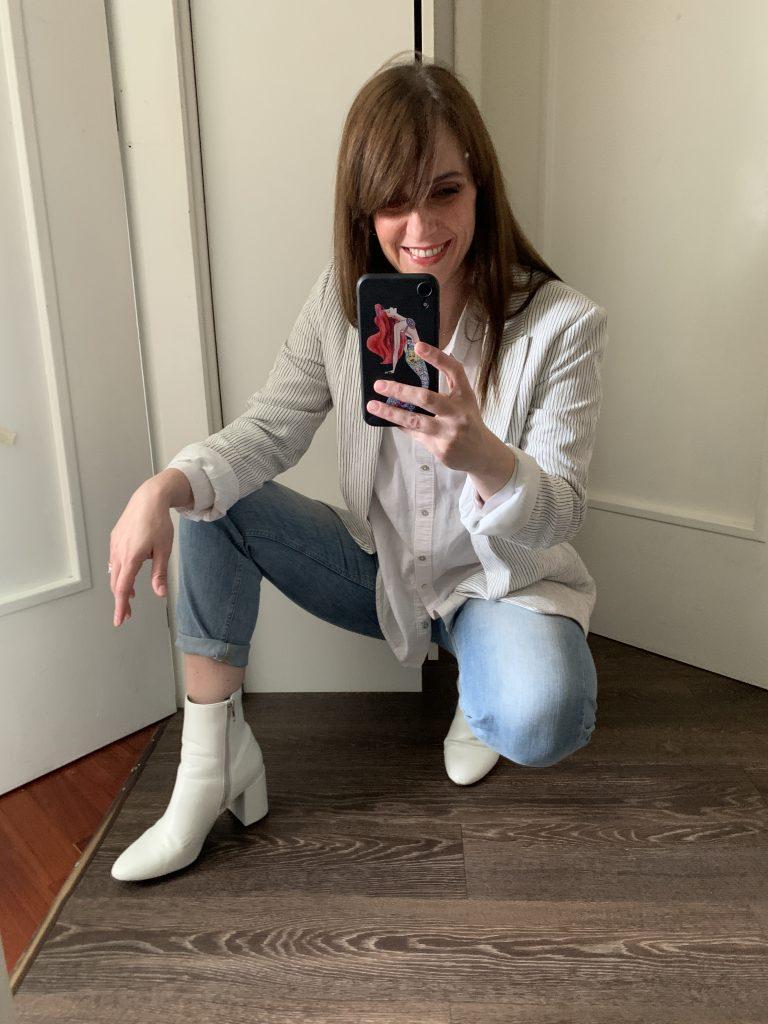 donna fa selfie davanti allo specchio.indossa stivaletti bianchi , momento jeans, camicia bianca over e una giacca in lino a righe blu. cosa comprare ai saldi è anche una scelta mentale