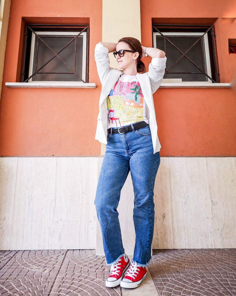 donna in posa davanti muro arancione . indossa denim flaire a vita alta una t-shirt bianca e una giacca in lino a righe blu. Ha le braccia alte dietro la testa e indossa Ray ban. cosa comprare ai saldi estivi