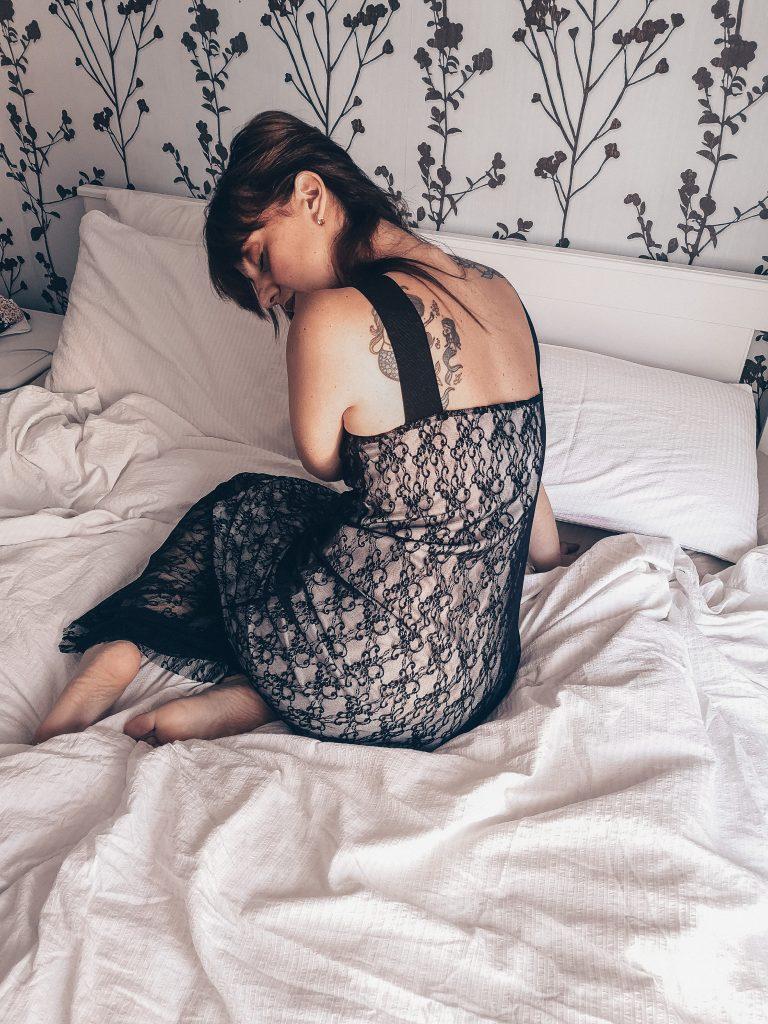 donna su letto disfatto con lenzuola bianche. indossa abito in pizzo nero con bretelle. è rannicchiata, con un amano si regge sul letto e con l'altra si tiene i capelli di lato. la sensualità femminile  un dono