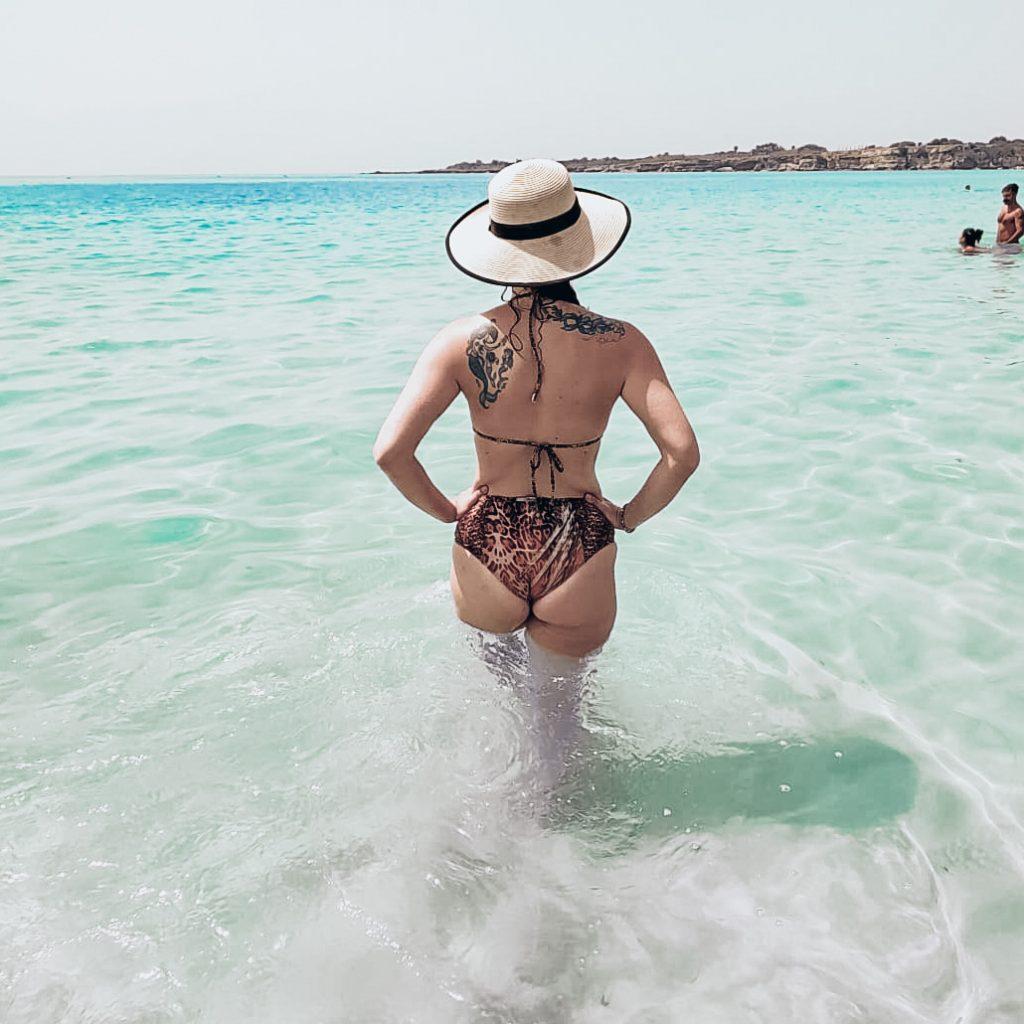 Donna al mare in piedi di spalle. è immersa fino alle anche. ha le mani poggiate sui fianchi e indossa un cappello di paglia a falda larga. indossa un bikini leopardato a vita alta. voglio essere bellissima  è uno dei desideri raggiorni di ogni donna