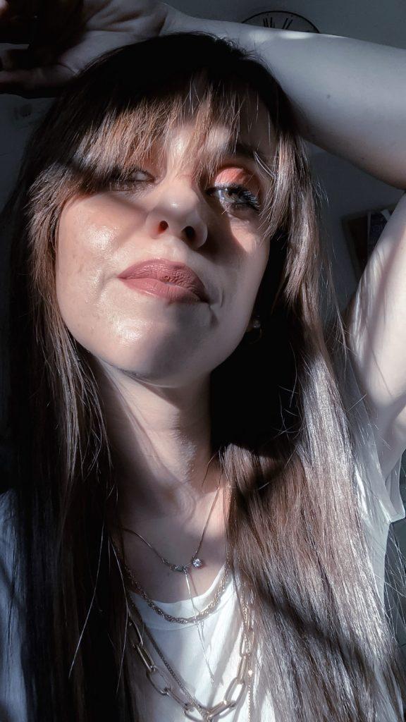 primo piano di donna in controluce, con ombra della persiana sul viso. indossa t-shirt bianca, collana multifido color oro, rossetto nude. ha i capelli lunghi che arrivano alle spalle e frangia lunga. una mano è alzata sulla tesa. voglio sentirmi bella è un desiderio di molte donne