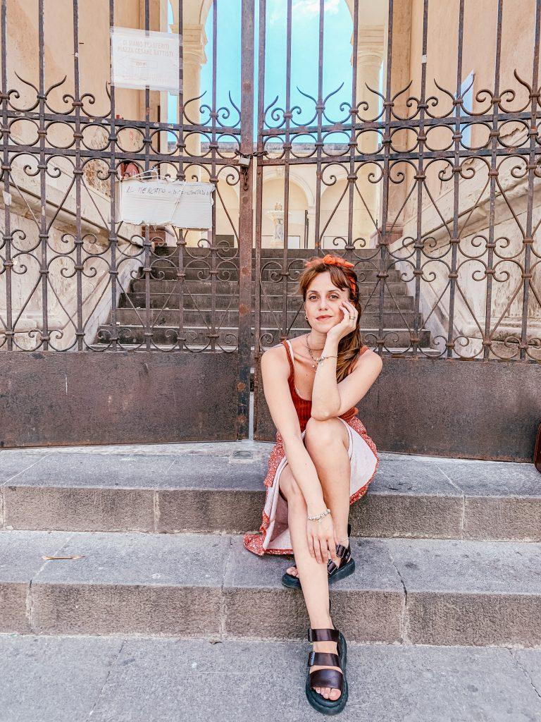 Donna seduta su scalinata davanti a cancello antico di un cortile. indossa sandali a fasce di pelle, una gonna midi arancione e canotta marrone. fascia in testa con nodo centrale. una mano regge il mento e l'altra è poggiata al ginocchio. voglio essere bellissima lo devi sentire anche interiormente