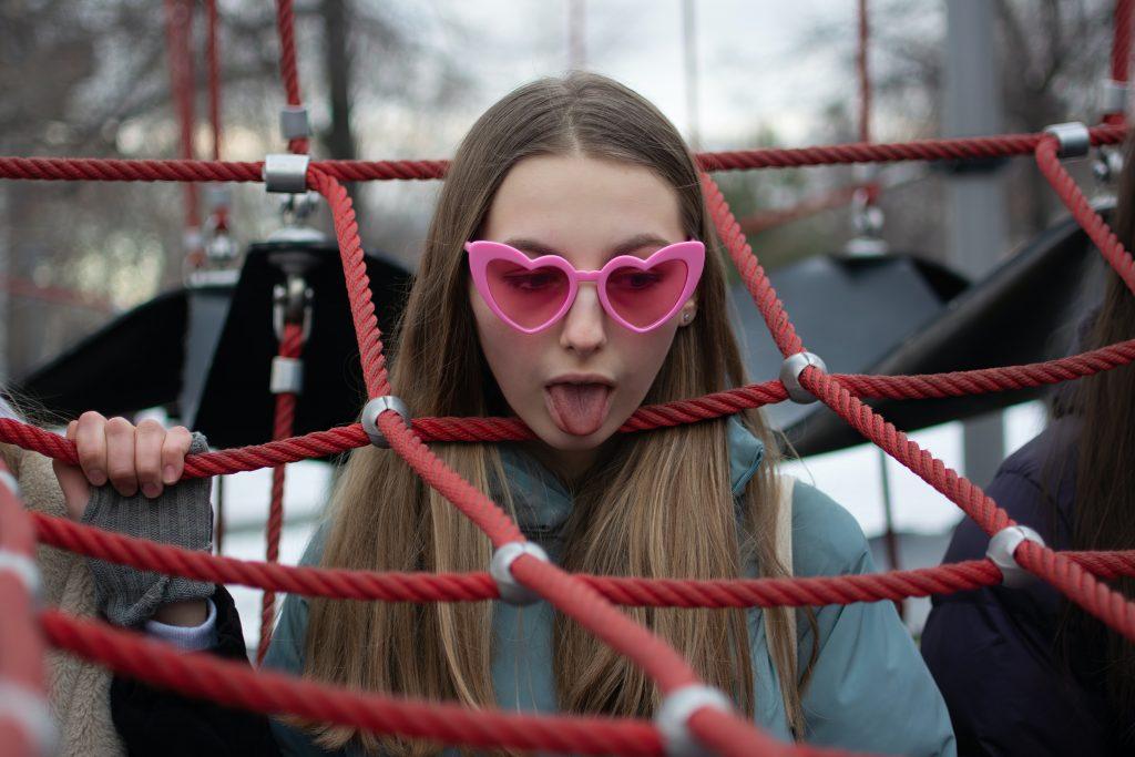 primo piano di ragazza tra le corse di una gioco per bambini. indossa occhiali a forma di cuore, jihadisti lunghi capelli sciolti. posa come se fosse strozzata da una corda e ha la lingua di fuori in segno di disgusto. diventare stronza per essere felice è possibile