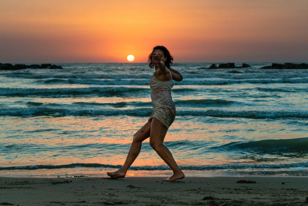 donna che balla su una spiaggia al tramonto. indossa un abito corto sottoveste. con la mano indica la fotocamera. inspira, resta e resiti: questo insegna la mi amindfulness