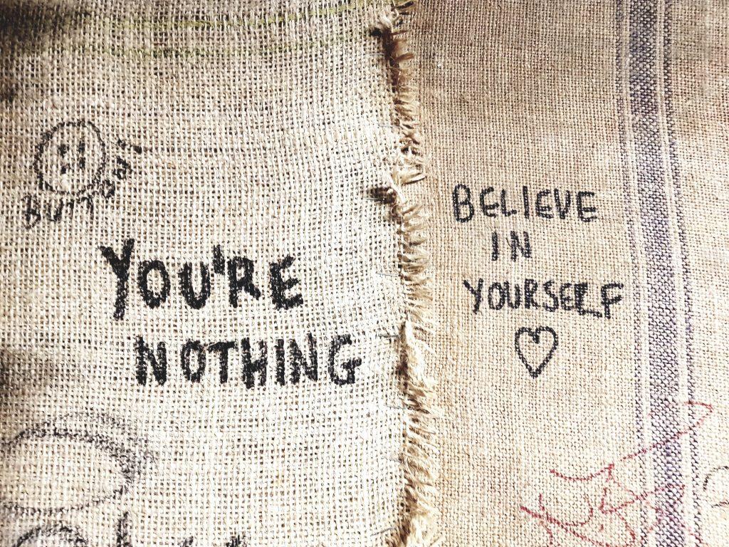 """stoffa di rafia in due colori con due scritte. da una parte """"you'e nothing"""" e dall'altra """"belline in yourself"""". inspira, resta e resisti: la mindfulness ti fa scegliere dove stare"""
