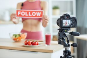 Blurred portrait of unrecognizable young woman holding FOLLOW sign while recording food video, focus on camera screen, copy space